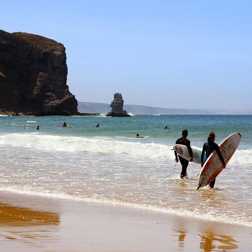 surfers ready to enter the sea in arrifana beach, algarve portugal